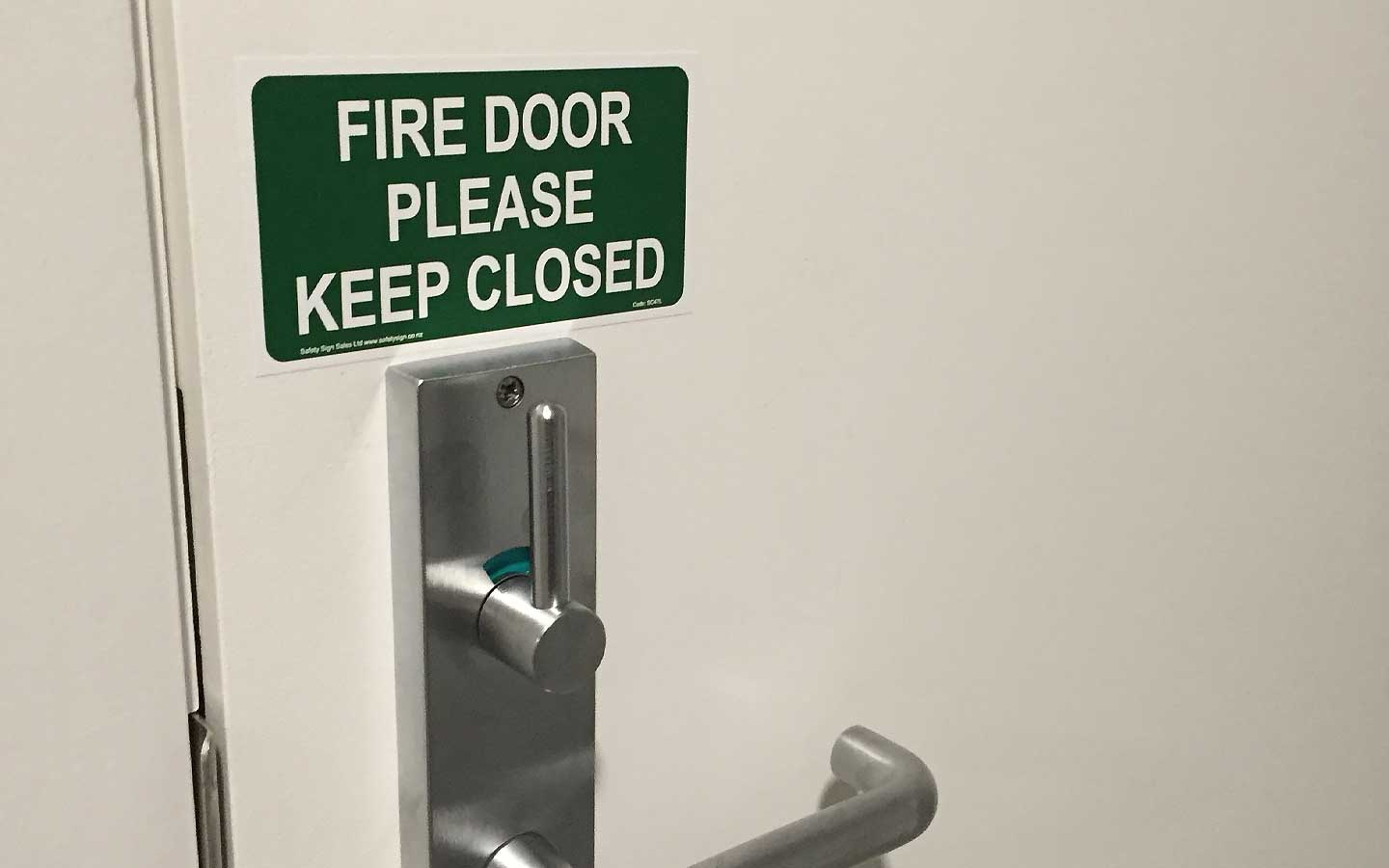 """A """"fire door please keep closed"""" sign on a door for building code compliance."""